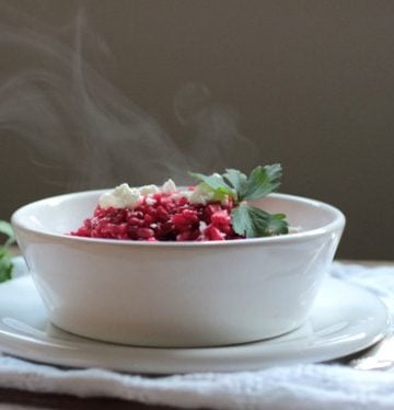 White bowl with steaming roasted beet risotto