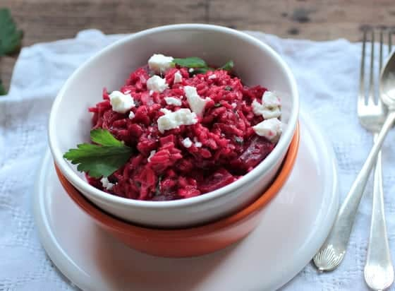 Roasted Beet Risotto in white and orange bowls on a white cloth, spoon and fork