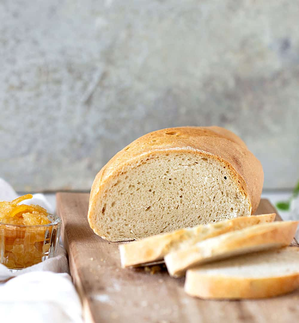 Half loaf and slices of semolina bread on wooden board with grey background