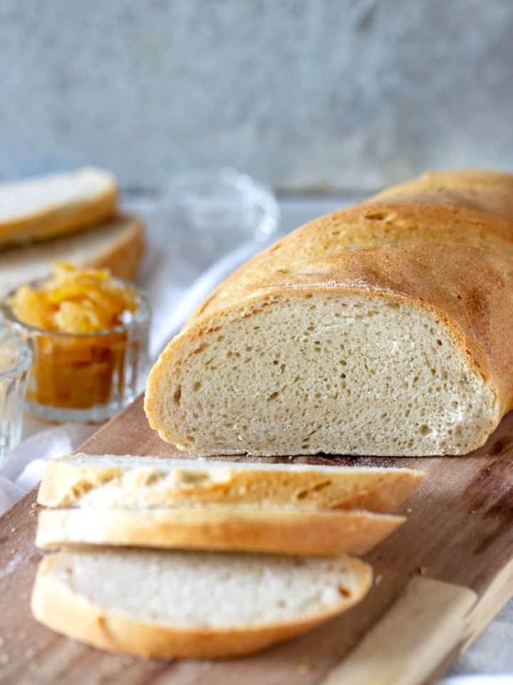 Half loaf and slices of semolina bread on wooden board, lemon jam