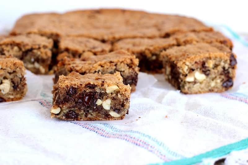 Squares of blondies with chocolate and peanuts on a white acqua kitchen towrl