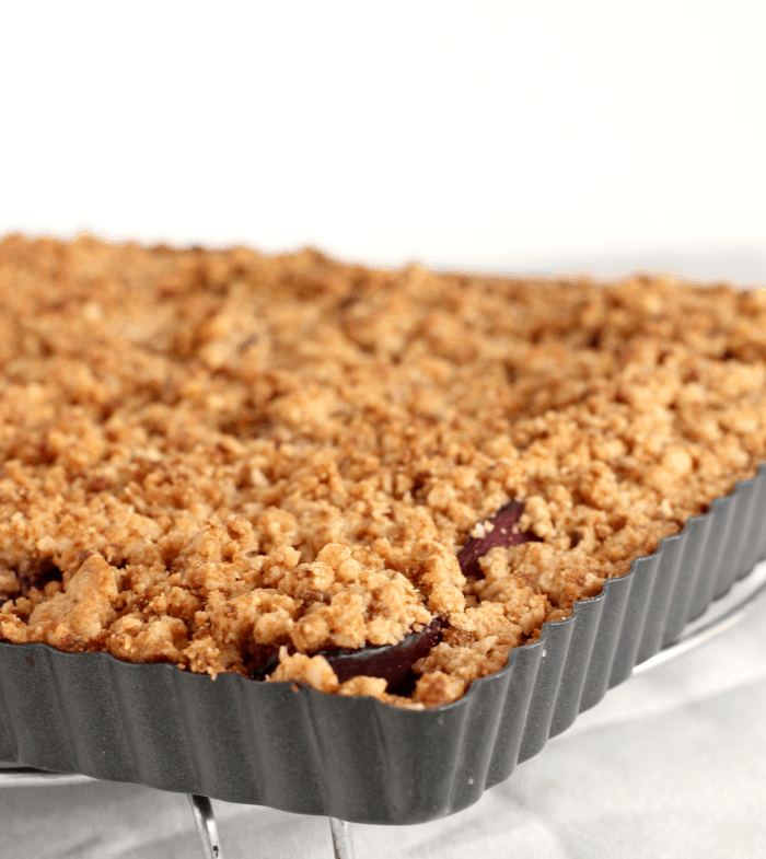 Corner of square tart pan with plum crumble tart