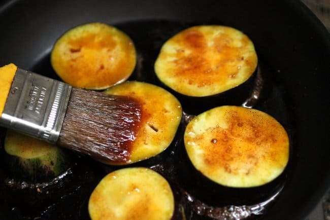 Brushing honey mixture over eggplant rounds in black skillet