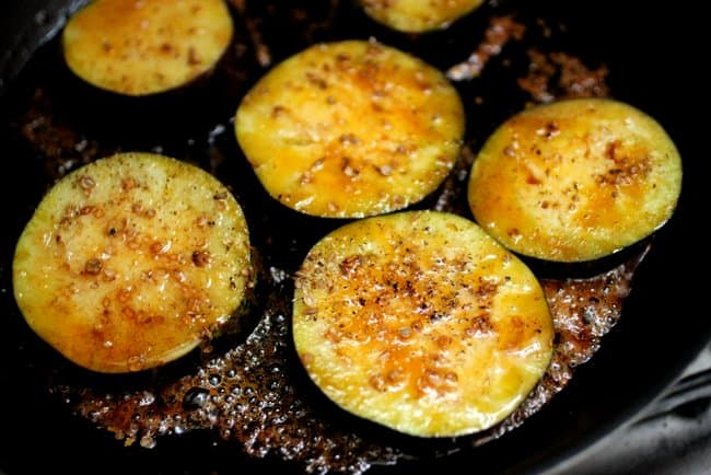 Cooking slices of eggplant with honey on a black skillet