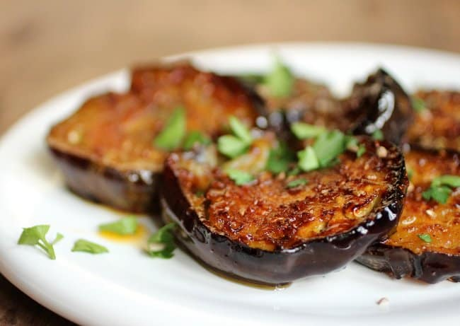 Close-up image of cookied eggplant sliced on a white plate, chopped herbs on top