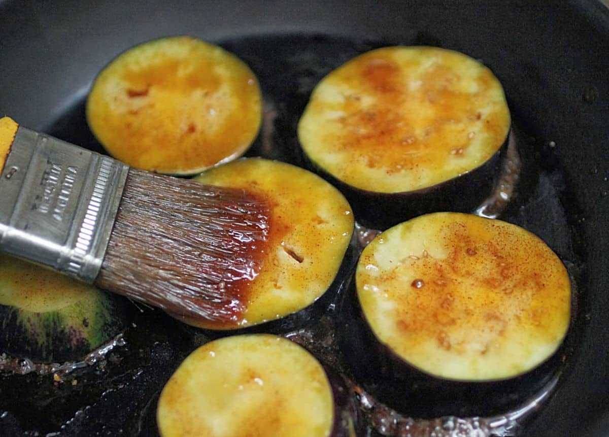 Brushing honey mixture over eggplant rounds in black skillet