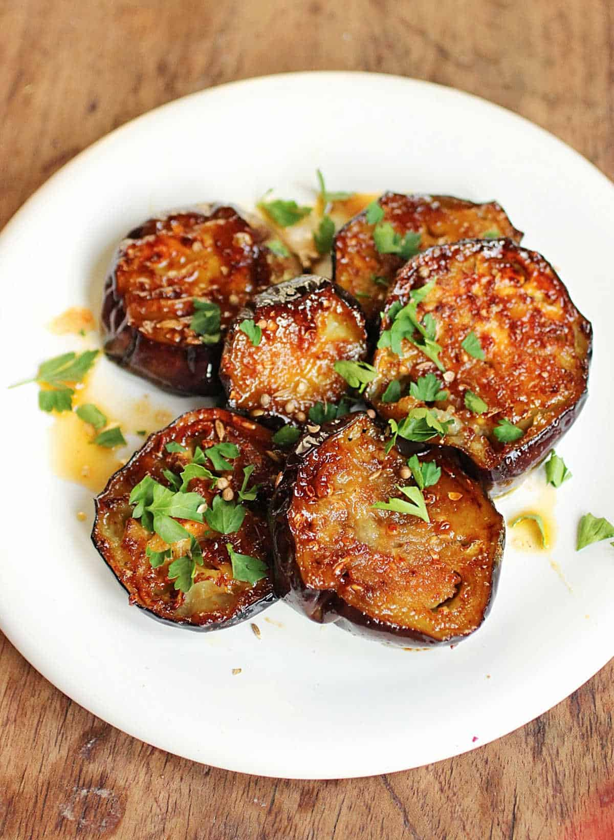Eggplant rounds with caramelized coating and chopped herbs on white plate, wooden table
