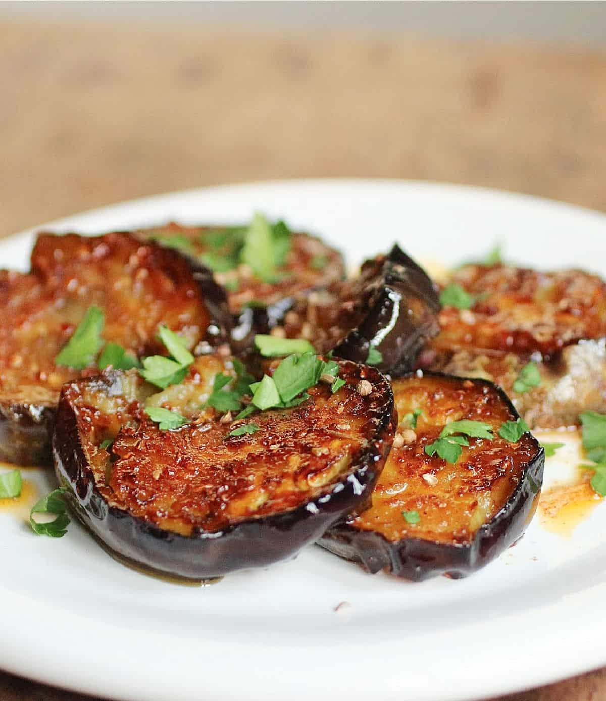 Partial view of white plate with eggplant rounds and herbs, wooden surface