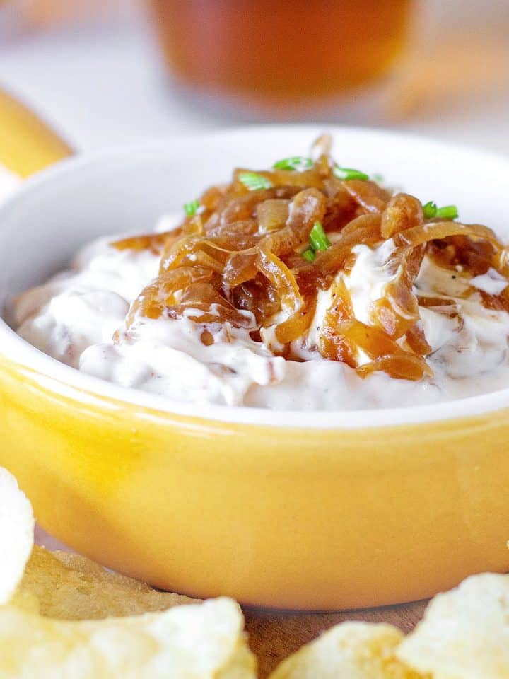 Yellow shallow ramekin with caramelized Onion Dip surrounded by potato chips