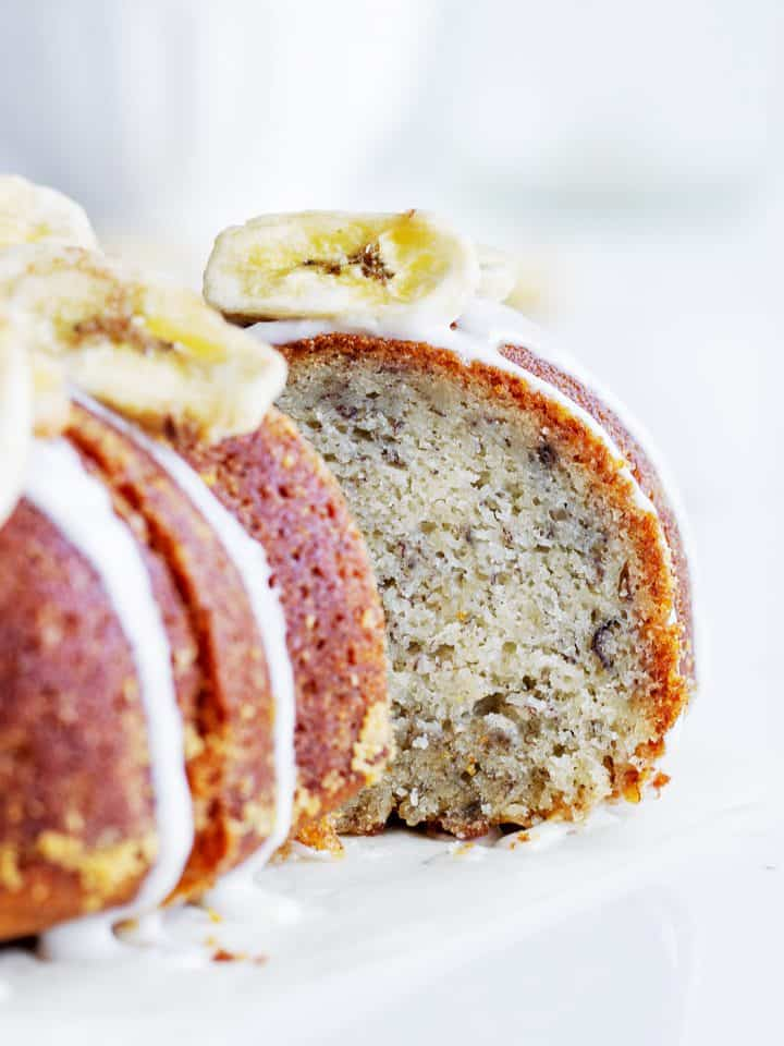 Slice of banana cake pulled out from whole glazed bundt, banana chips on top, white background