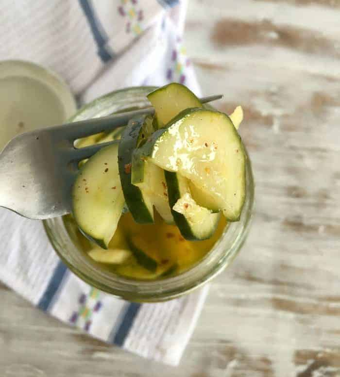 Lifting Pickled Cucumbers with a fork from glass jar, kitchen towel below on whitish table