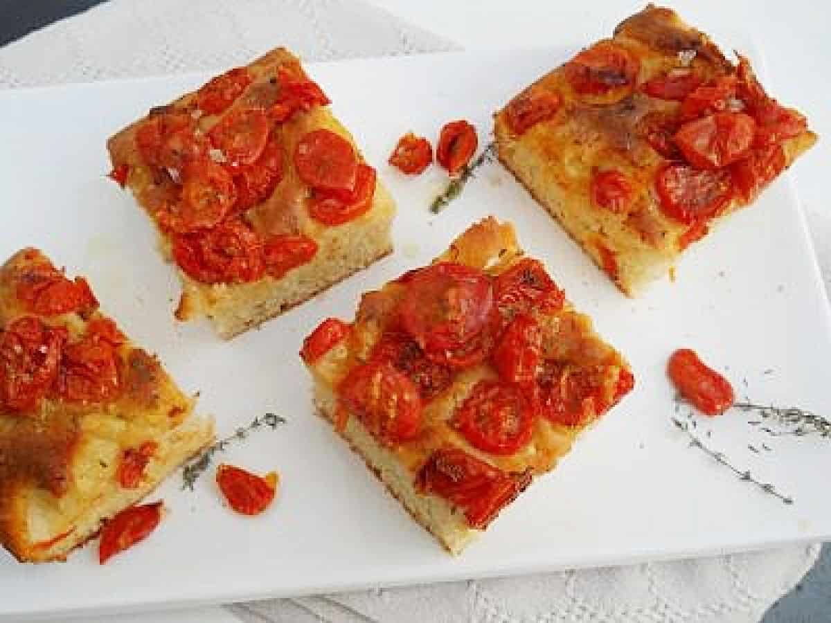 Top view of several squares of tomato bread on white plate