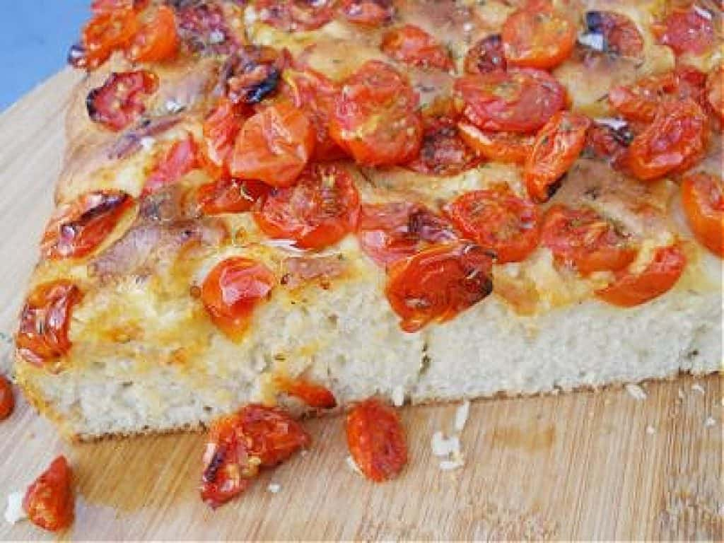 Slab of focaccia bread topped with tomatoes on wooden board