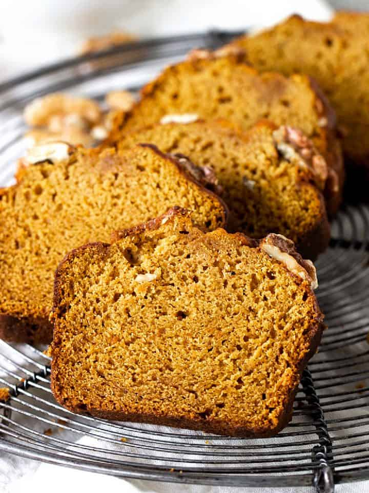 Slices of pumpkin bread on dark metal wire rack, walnuts, white surface