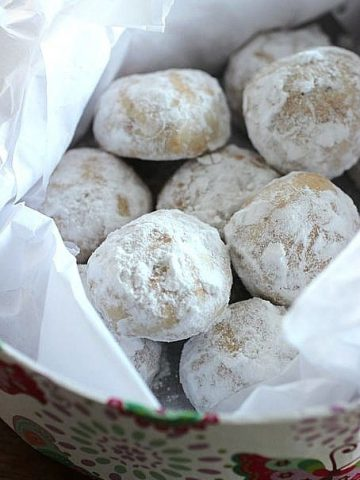Several powdered sugar cookies with white parchment paper in a box