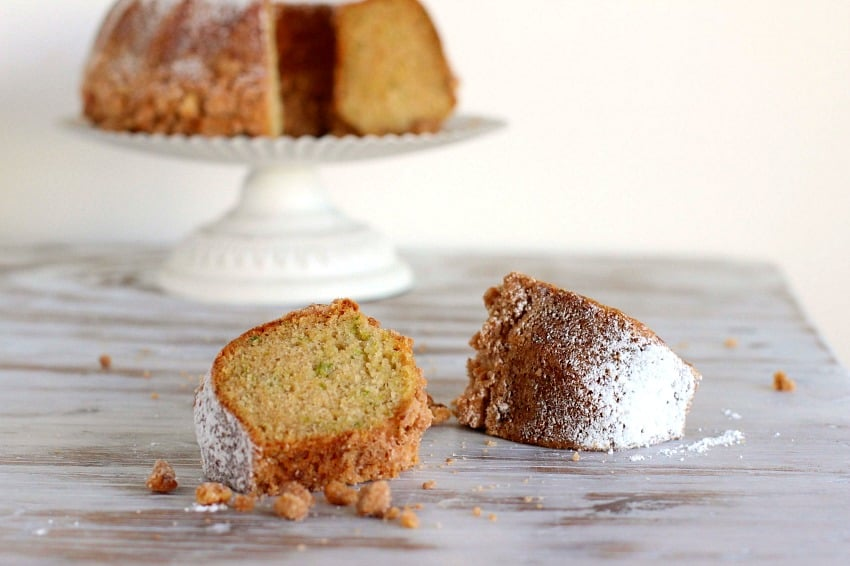 Two slices of zucchini bundt cake on white table, cake on white stand in background