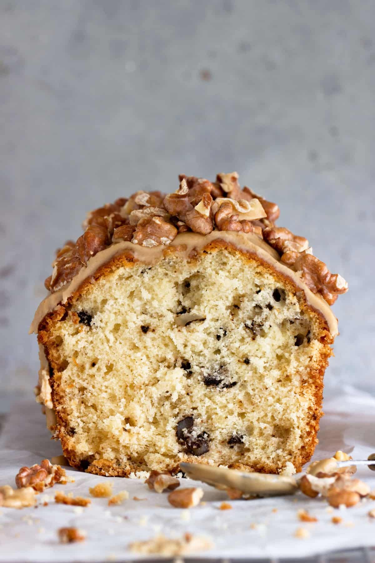 Half loaf cake with walnuts on top, grey background, loose walnut pieces