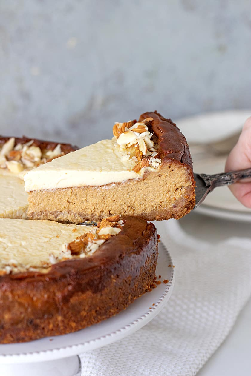 Lifting slice of Brown Sugar Cheesecake from cake on white cake stand