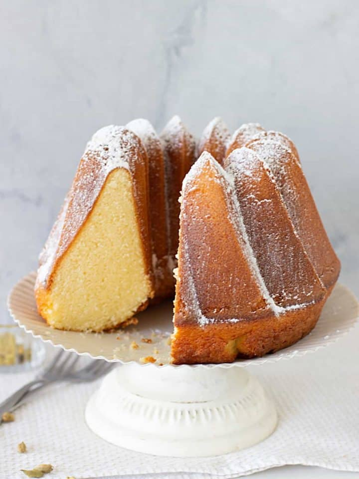 Cardamom Bundt Cake in a white cake stand, one piece missing
