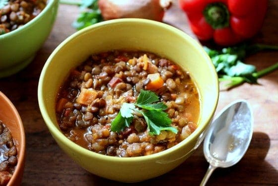 Yellow bowl with Lentil stew, silver spoon, vegetables in background