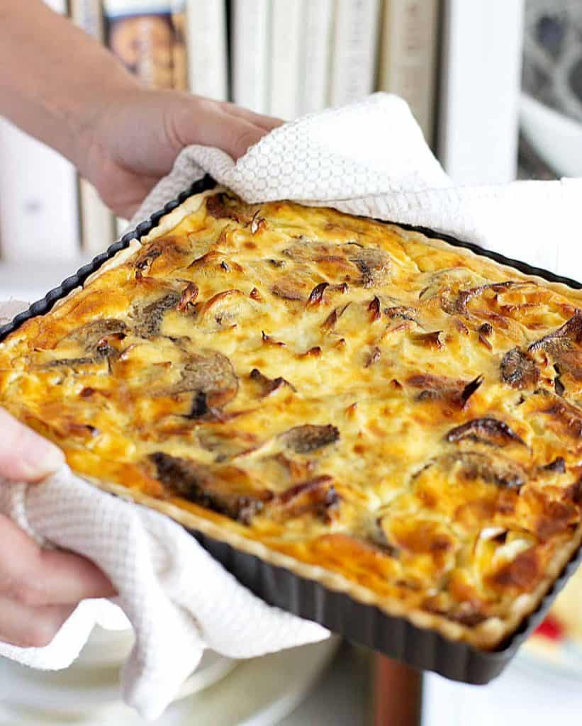 Hands holding square mushroom quiche still in metal pan