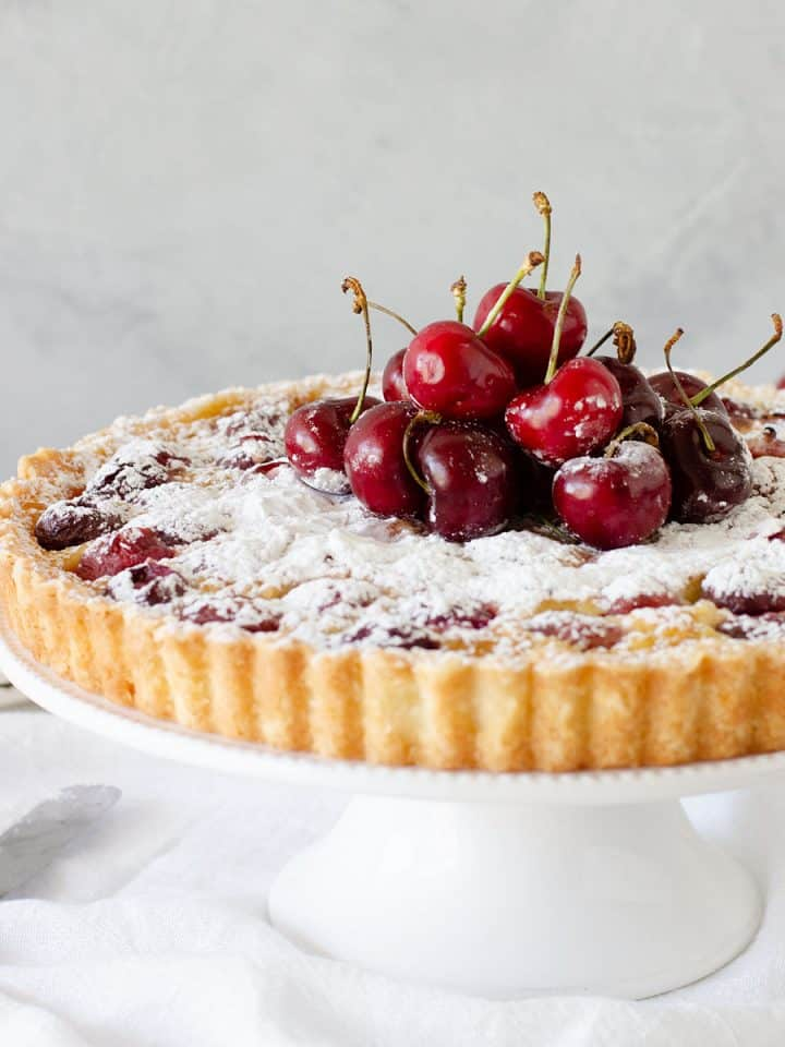 Front view of cherry tart on white cake stand, grey background