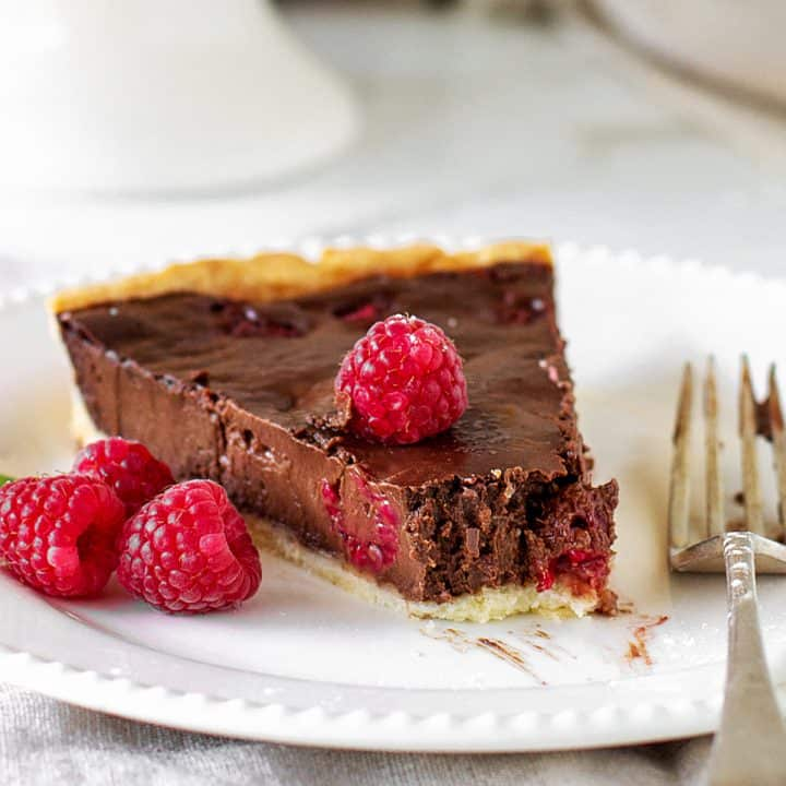 Slice of chocolate raspberry tart on white plate, silver fork