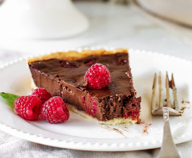 Slice of chocolate raspberry tart on white plate, silver fork