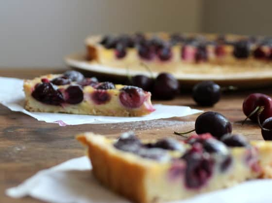 Bill Granger's Fresh Cherry Tart slices on wooden table