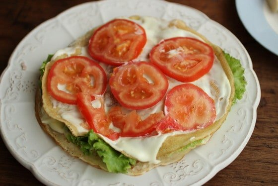 Building crepe cake with slices of tomato, mayonnaise and lettuce on white plate