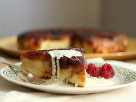 Whitish plate with single serving of apple bread pudding, fork, whole pudding blurred in background