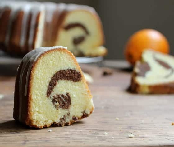 Slice of marble bundt cake on wooden table; rest of cake and orange blurred in the background