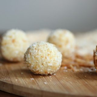 White Chocolate Truffles coated in shredded coconut on a wooden board