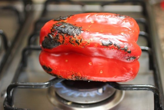 Whole Red pepper being charred in the stove