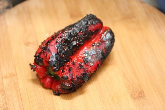 Charred red bell pepper on wooden board