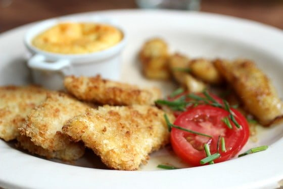 Close-up of chicken fingers with tomato slices, blurred corn pudding