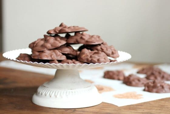 Chocolate peanut mounds on white cake stand, some on paper below, wooden table