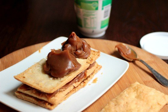 Mounds of dulce de leche on top of puff pastry rectangle on white plate