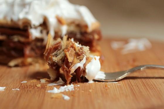 Fork with bite of dulce de leche meringue dessert on wooden board