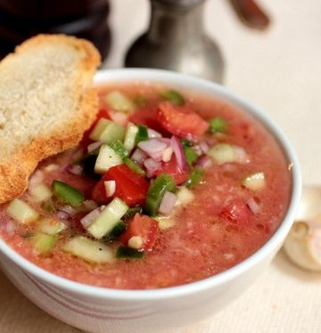 White bowl with cold tomato soup, slice of bread on top, loose garlic cloves around