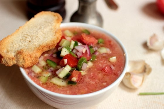 white bowl of tomato soup with cucumber relish, slice of bread on top