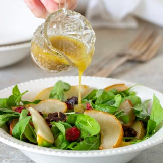 Pouring vinaigrette over pear arugula salad on white bowl plate