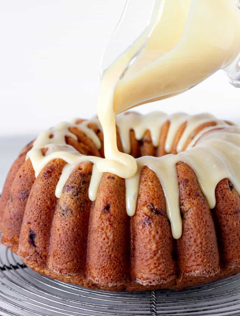 Pouring white chocolate ganache on a bundt cake on a wire rack