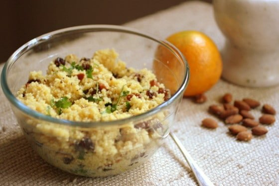 Glass bowl with Orange Couscous, cream surface, loose almonds, whole orange