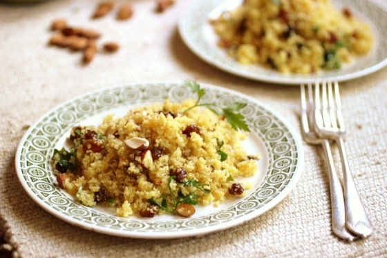 Two plates with Orange Couscous on cream surface, forks, loose almonds