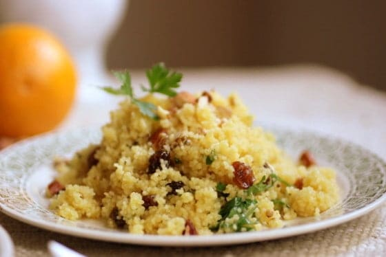 Mound of couscous with raisins, nuts and parsley on a green white plate, whole orange in background