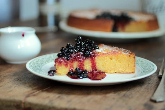 Slice of Lemon Polenta Cake with blueberry sauce on white plate, wooden table, saucer