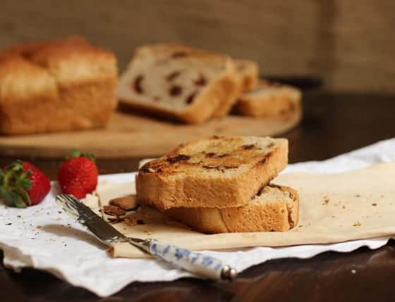 Slices of loaf bread on napkins, a butter knife, strawberries and loaf in the background
