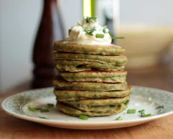 Stack of chard pancakes on a plate, sour cream and chive garnish