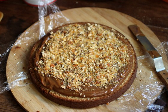 Praline and dulce de leche top a round of cake, plastic wrap and wooden board beneath